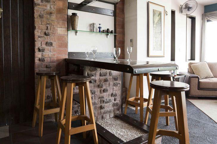 Уголок стиля лофт в гостиной. Всё по классике дизайна-старая кладка кирпича, затёртая барная стойка.