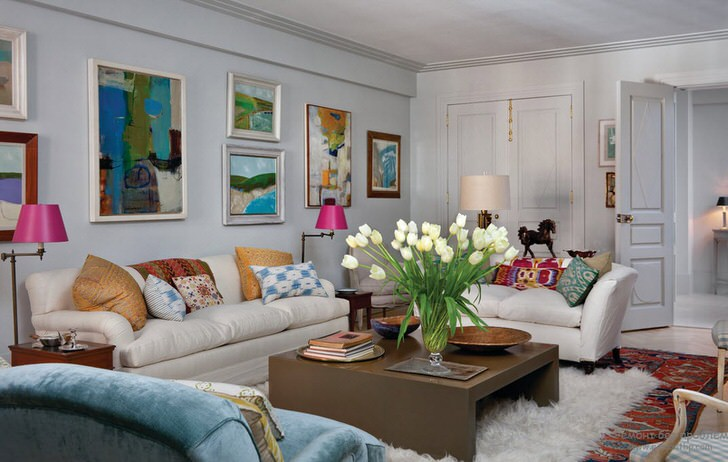 Универсальная гостиная в стиле эклектика. Уютной комнату делают множество подушек и абстрактные, яркие картины, которые украшают стену над диваном.