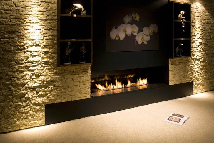 Встроенный в декоративную отделку стены вытянутый камин гармонично вписывается в интерьер современной комнаты.