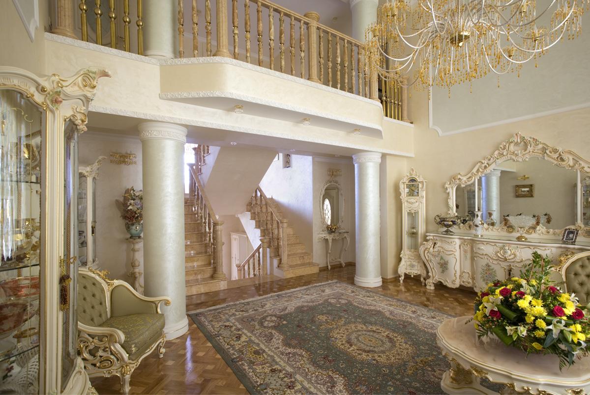 Гостиная в барокко стиле примечательна колоннами небольшим выступающим балконом на втором этаже.