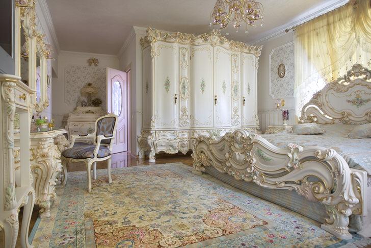 Белоснежная спальная комната с резной массивной мебелью из дерева. Кровать с высокой спинкой у изголовья, шикарно вписывается в интерьер в стиле барокко.