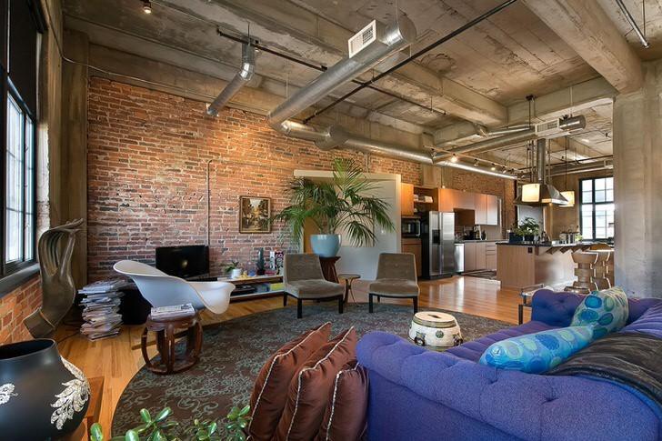 Характерная просторная гостиная в стиле ЛОФТ. Кирпичная стена, вентиляционные трубы остаются в первозданном виде.