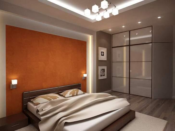 Функциональная спальня с удачно подобранным освещением выполнена в серых и светло-бежевых тонах.