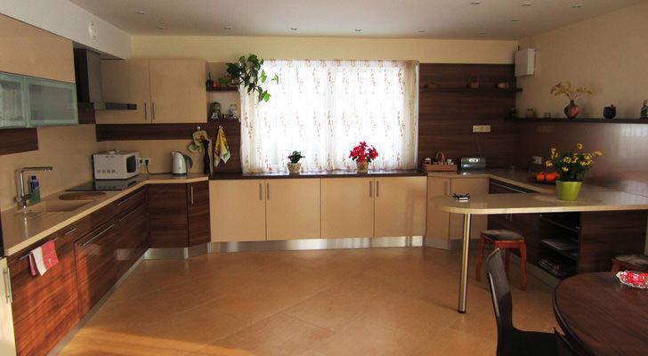 Приятная большая кухня в светлых бежевых тонах с акцентами красного дерева удобной мебели.