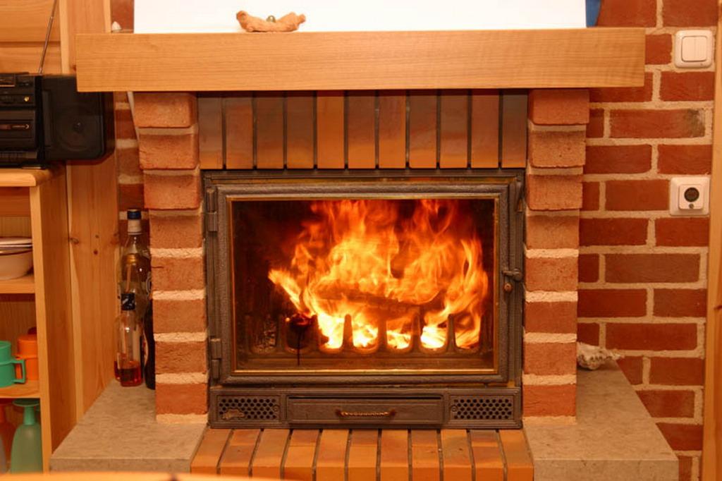Кирпичный камин с имитацией огня не только достойно выглядит, но и обогревает комнату.