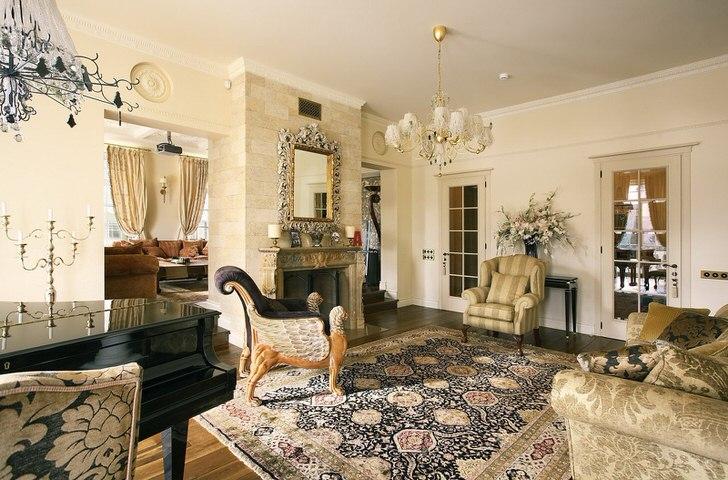 Шикарная гостиная в стиле ампир с камином из природного камня. Яркие темно-синие элементы оформления смотрятся контрастно на бледно-бежевом фоне, притягивая взгляд.