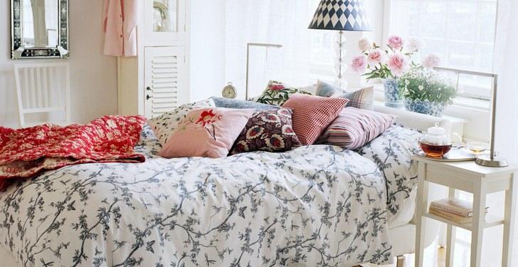 Правильно декорированная в стиле кантри кровать. В лучших традициях кантри на спальном месте сложены подушки контрастных цветов и плед.
