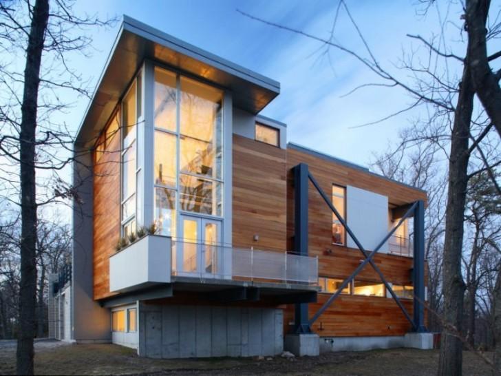 Деревянные стены дома в стиле хай-тек со стильными пластиковыми панорамными окнами.