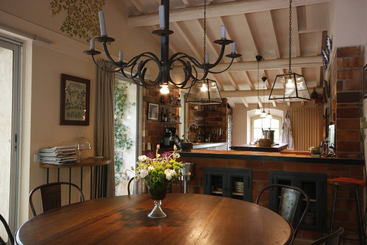 Обеденная и кухонная зона оформлены в кантри стиле. Что примечательно, над столом висит люстра, которая освещает пространство с помощью обычных восковых свечей. Тонкая дизайнерская задумка, ведь в комнате имеется и традиционное освещение, работающее от электрической сети.