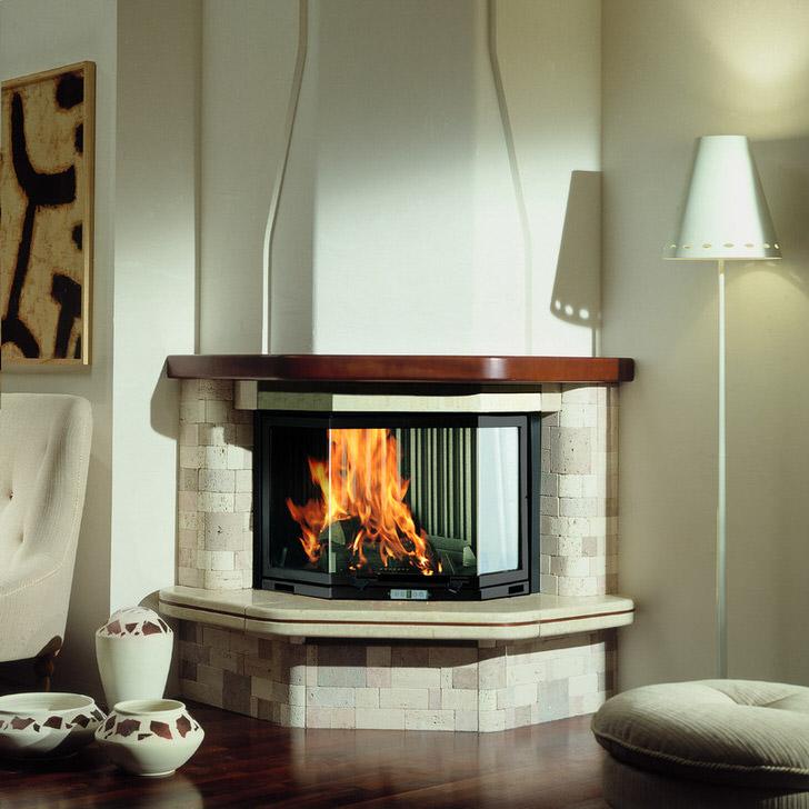 Угловой камин удачно гармонирует с интерьером тёплого средиземноморского стиля. Дымоход и портал из светлого кирпича создают умиротворяющее настроение. просторной гостиной