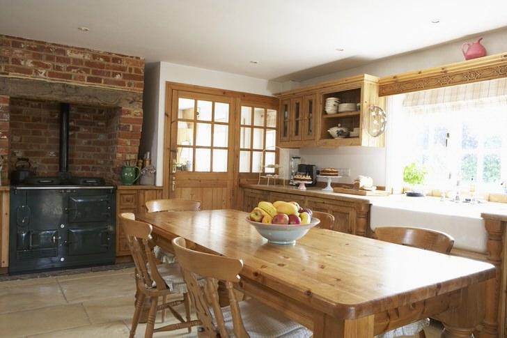 Просторная кухня в стиле кантри. Деревянная мебель и кирпичная отделка над печкой придают стилю естественности и романтичности.