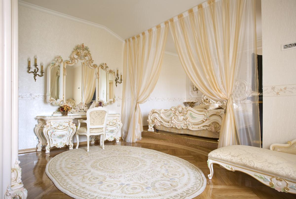Обрамление зеркал и декоративные элементы мебели выполнены в одном стиле с использованием золота. С целью экономии пространства кровать спрятана в нишу, обрамленную шторами.