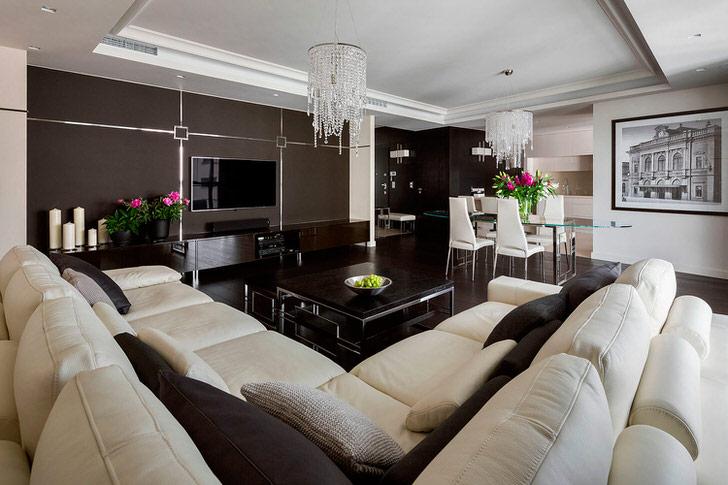 В интерьере гостиной соперничают два цвета белый и коричневый. Дизайнер решает проблему картиной, люстрами и цветами.