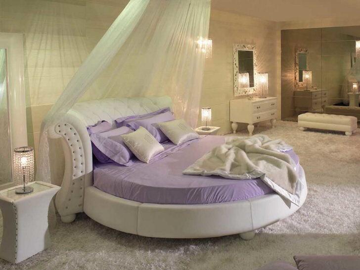 Оригинальная круглая мягкая кровать под полупрозрачным балдахином.