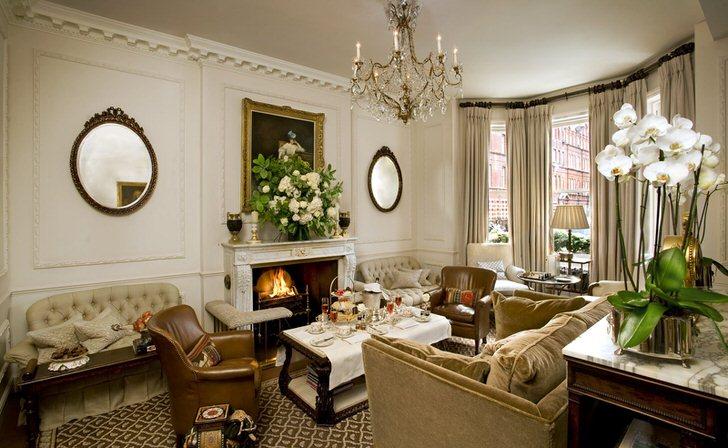 Сдержанно роскошная, просторная гостиная в престижном доме Манчестера. Элегантный камин ненавязчиво является центром притяжения в дизайне интерьера комнаты.