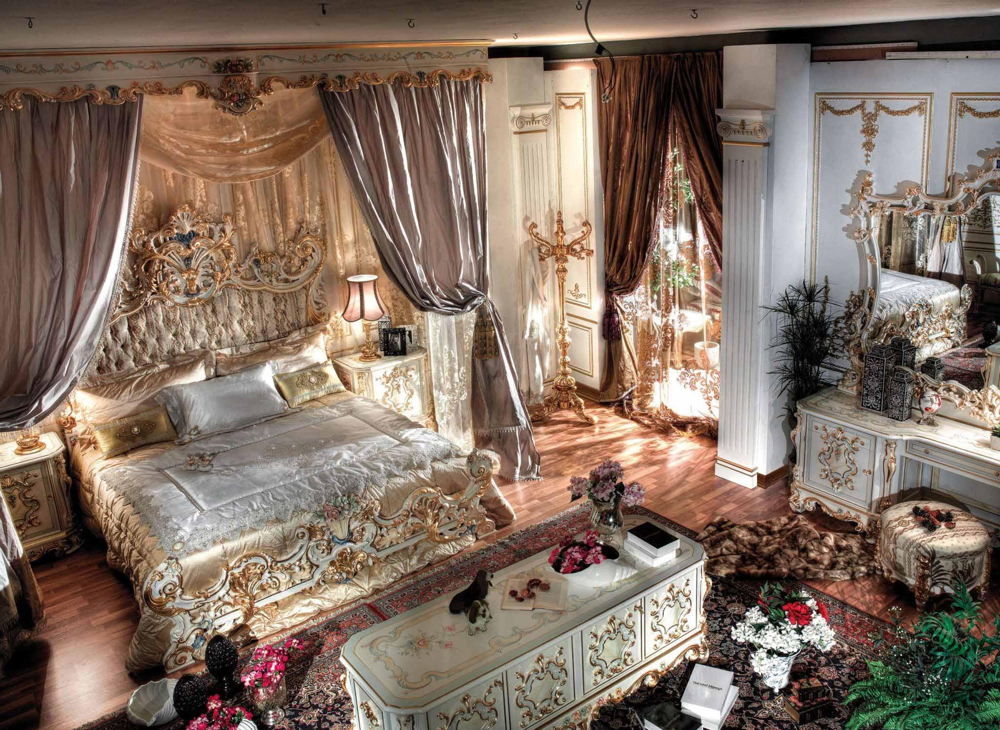 Роскошная спальня в стиле барокко с высокими потолками. В центра композиции массивная кровать из дерева с резными спинками.