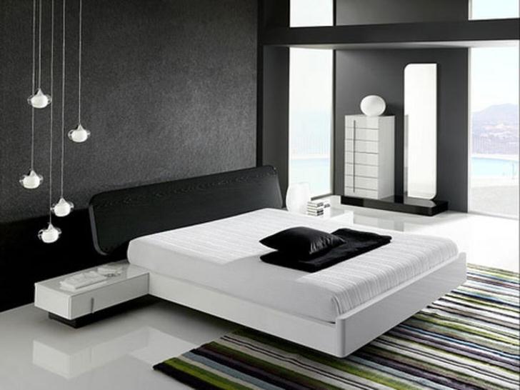 Стена у изголовья кровати, декорированная серой матовой вставкой, в соответствии со стилем хай-тек гармонирует с глянцевым белым полом.