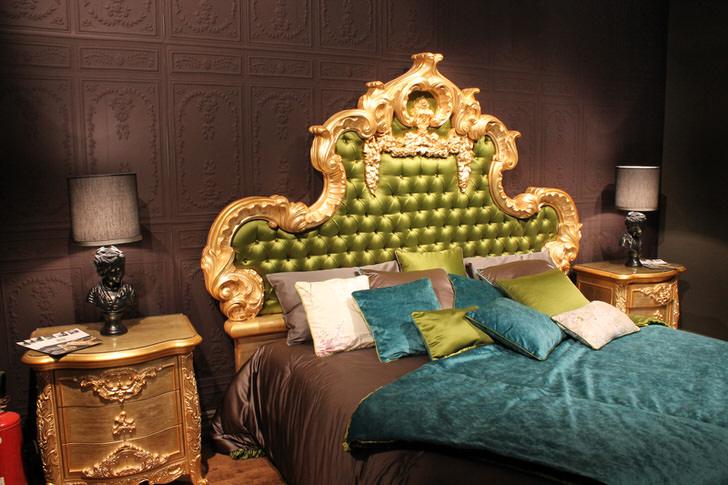 Высокая витиеватая спинка в изголовье кровати обита шелком оливкового цвета. Интересны подушки контрастных цветов и покрывала на кровати.