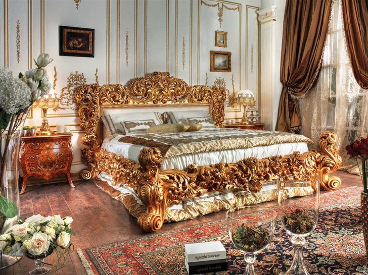 Шикарная кровать выполнена в лучших традициях стиля ампир. Массивные спинки кровати из резного дерева благородного золотого цвета выделяются на фоне остальных деталей интерьера.