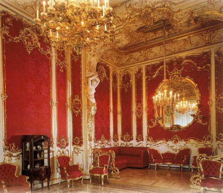 Гостиная в доме правильно декорирована мебелью красного цвета. Благородный красный отлично сочетается с золотыми элементами отделки.