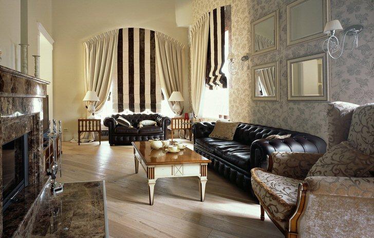Пример оформления гостиной. Дизайнер в центр интерьера поставил роскошные кожаные диваны Честер и обыграл их светлыми обоями.
