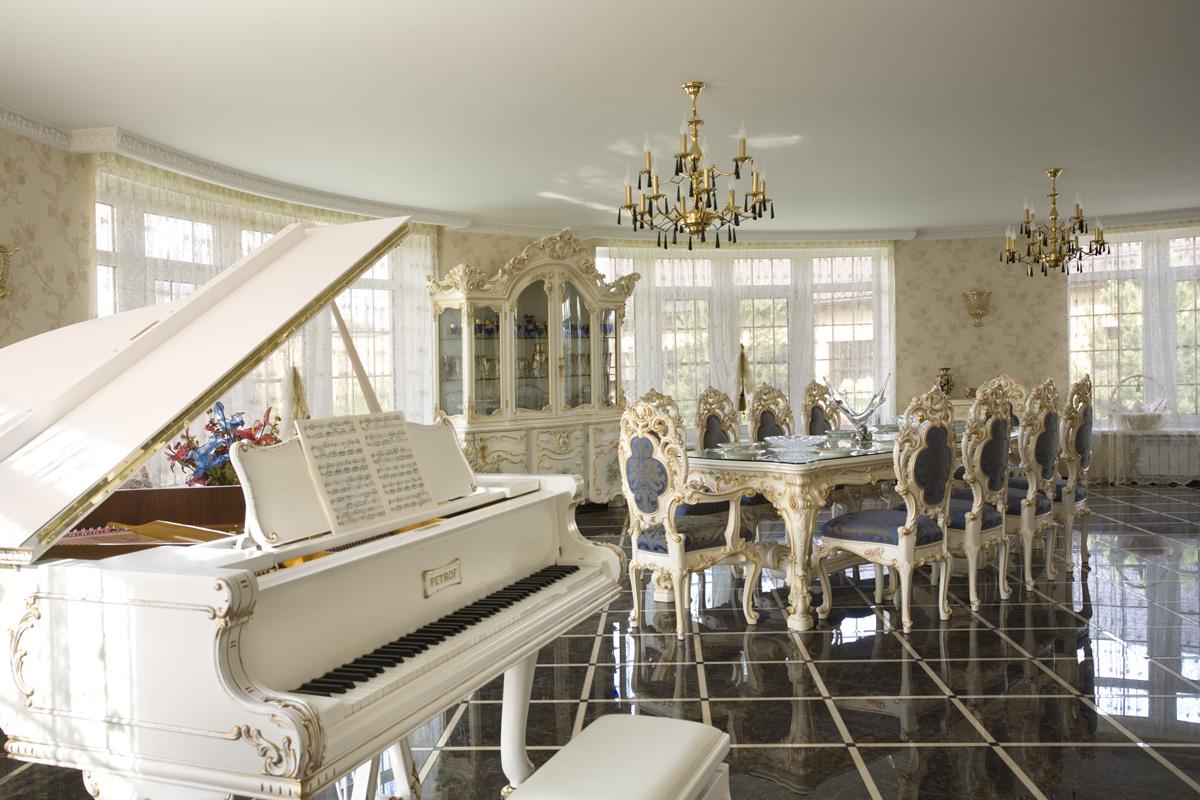 Просторная обеденная комната в барокко стиле. Владелец загородного дома, скорее всего, играет на фортепиано, которое идеально вписывается в общую картину интерьера.