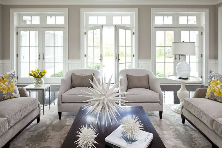 Гостиная в большом доме в стиле американский кантри примечательна массивной мебелью и панорамными окнами. Желтые цветы на столе и рисунок в тон на подушках стали главной изюминкой концепта.