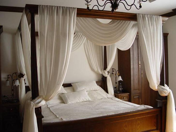 Белый балдахин над простой, лаконичной кроватью из дерева.