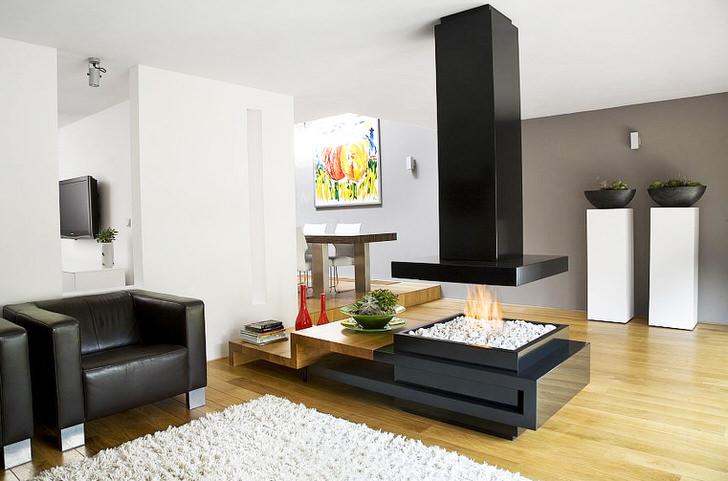 Стильный современный камин в стиле хай тек разделяет зону отдыха и столовую просторной гостиной.