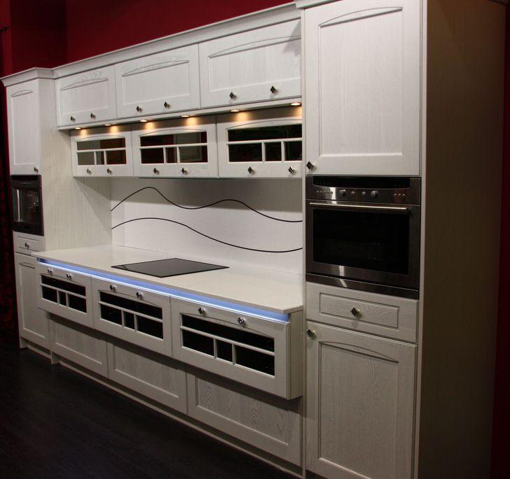 Кухонный гарнитур, несмотря на наличие ручек, станет идеально в интерьер кухни в авангардном стиле. Примечательно также точечное освещение рабочей поверхности и неоновая подсветка.
