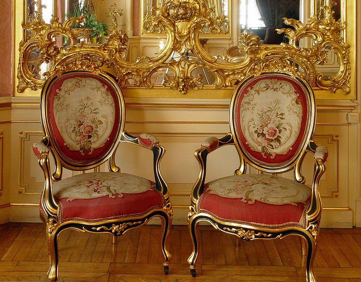 Ажурная лепнина золотого цвета на зеркале и стулья с красной мягкой обивкой - яркие представители стиля барокко.