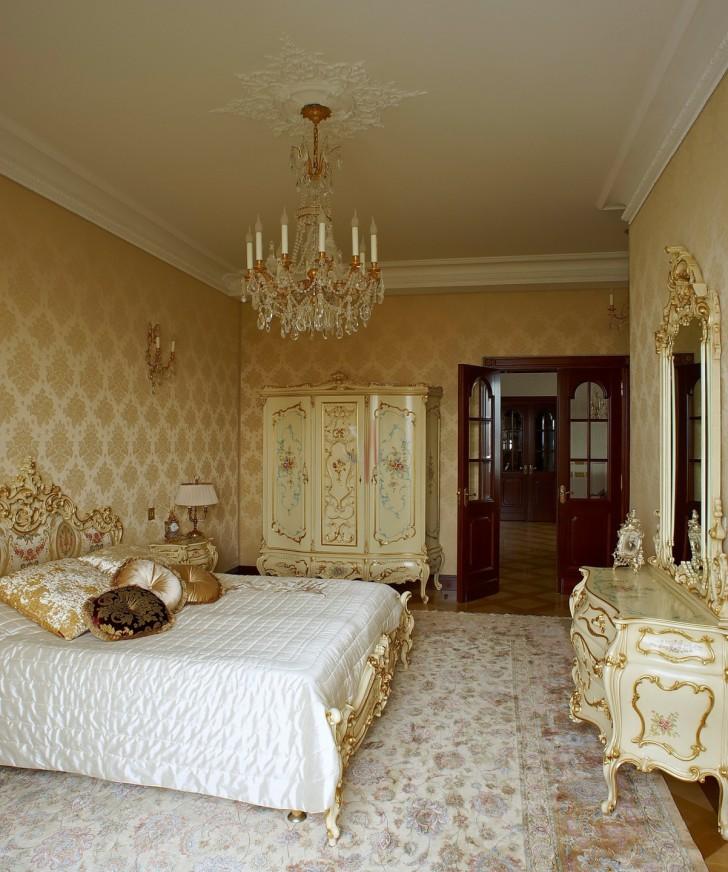 Шикарная люстра и потолок с лепниной гармонично сочетаются с деревянной мебелью в золотых тонах.