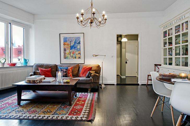 Стильная комната для гостей в обычной городской квартире декорирована яркими подушками на диване и ковром.