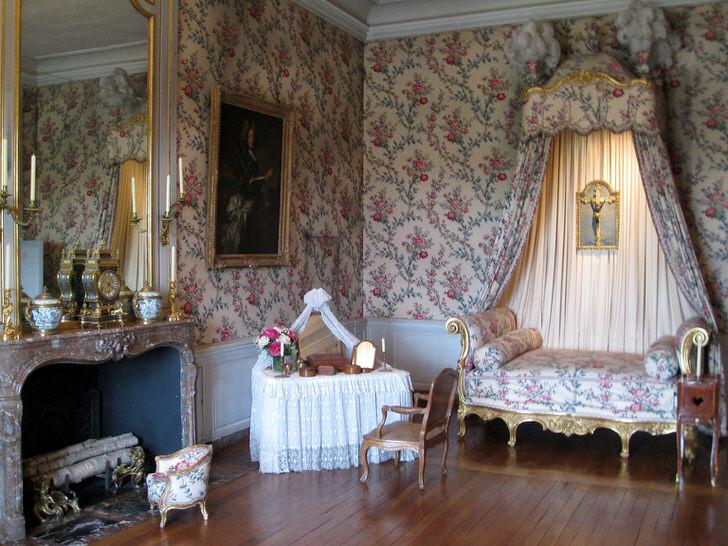 Красочная отделка стен гармонично сочетается с обивкой софы и балдахином над ней. Комната для отдыха в стиле барокко с большим камином - отличная идея для загородного дома.