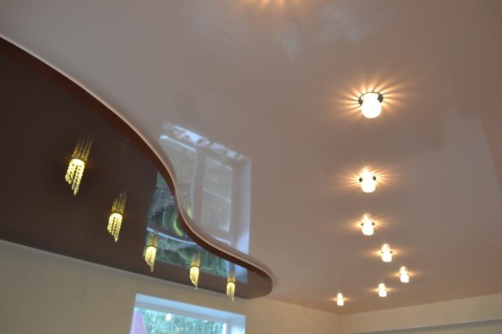 Оригинально продуманные дорожки освещения для двухуровневого потолка. Под темно-вишневой вставкой напрашивается установка барной стойки.