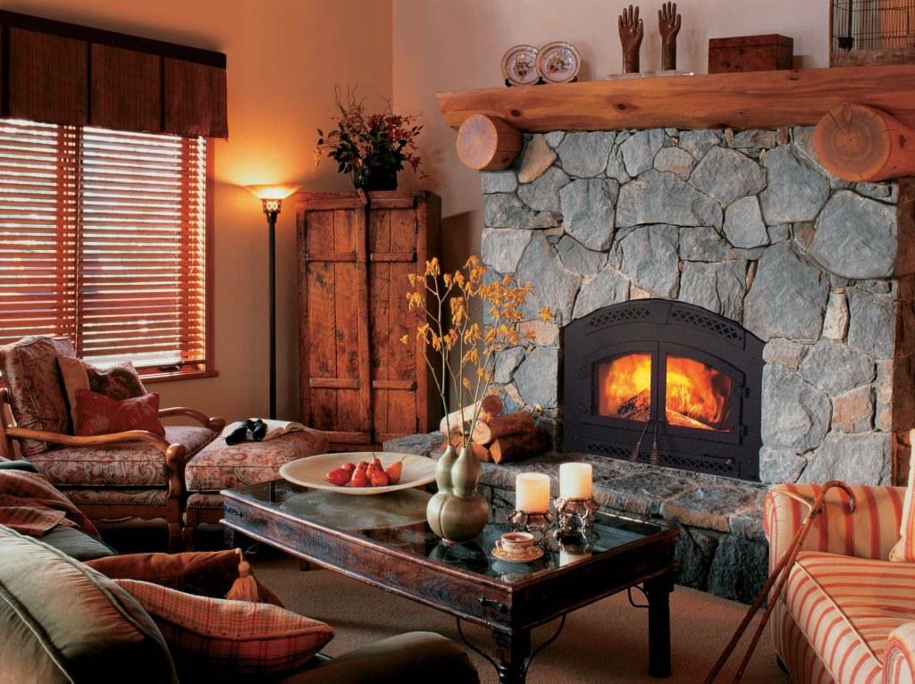 Громоздкий камин, оформленный с помощью деревянного сруба, гармонично вписывается в гостевую комнату в стиле кантри.