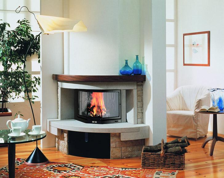 Чтобы камин не стоял одиноко в центре гостиной можно поставить угловые стенки и вся конструкция гармонично впишется в дизайн интерьера.
