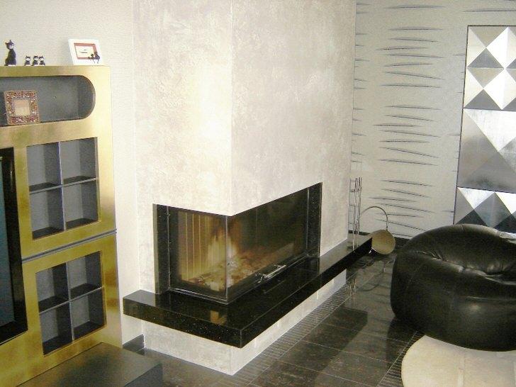 Современный угловой камин на внешней стороне угла в интерьере гостиной в стиле минимализм.