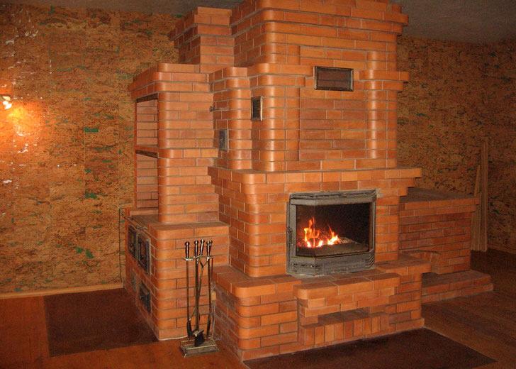Камин с литой чугунной топкой и массивным порталом из кирпича надолго согреет дом.
