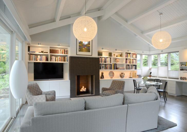 """Центр притяжения """"воздушного"""" загородного дома-камин с большими свечами. Мебель зоны отдыха в фокусе камина."""