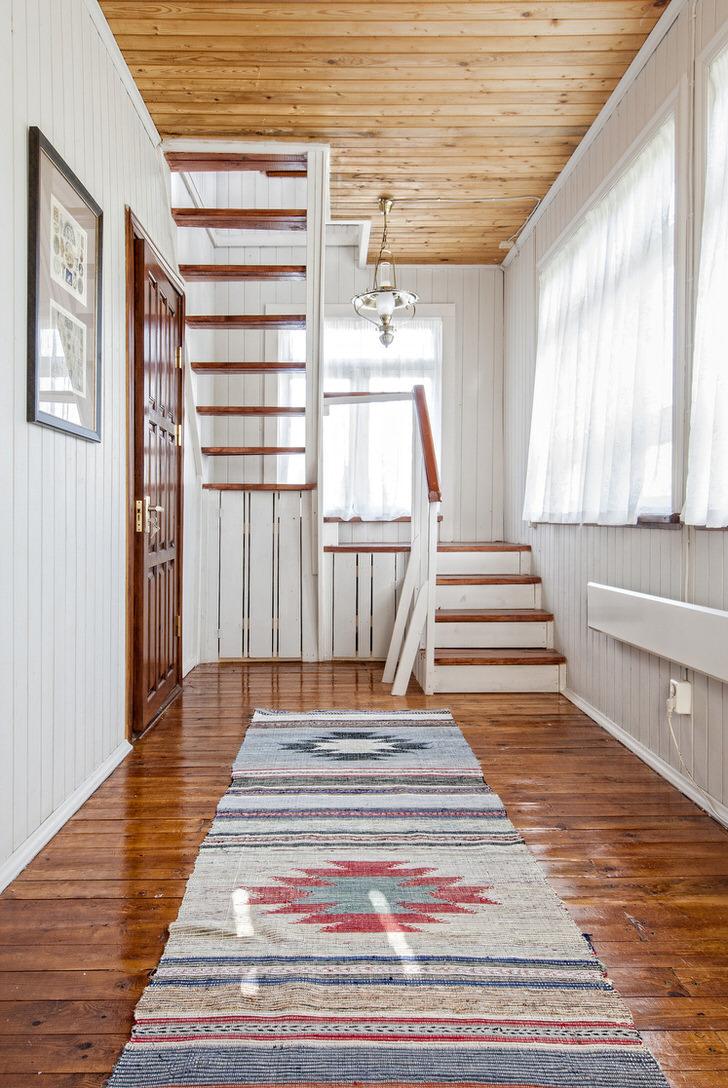 Отличный пример оформления прихожей и лестнице в загородном доме. Лестница из темно-коричневого и белого дерева отлично вписывается в общий колорит.