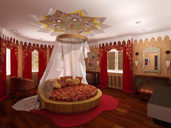 В центре композиции круглая кровать под балдахином. Внимание притягивает потолок, который интересно декорирован над кроватью.