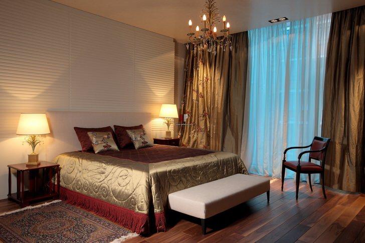 Традиционное освещение спальники в классическом стиле-люстра и привычные плафоны по бокам кровати.
