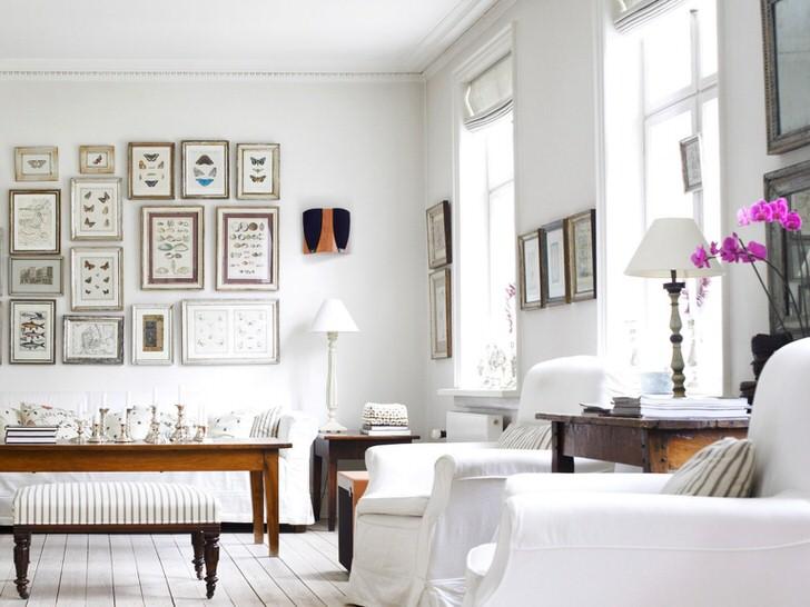Уютная гостиная в скандинавском стиле выполнена в белом цвете. Интересно оформление стены с помощью рамок разного размера.