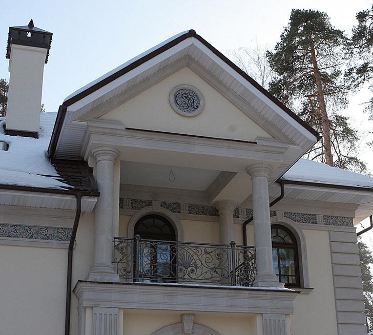 Витые кованные перила балкона органично сочетаются с массивными колонами.