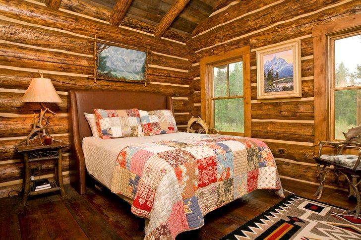 Спальня в деревенском стиле в охотничьем домике. Примечательно оформление стен при помощи сруба дерева.