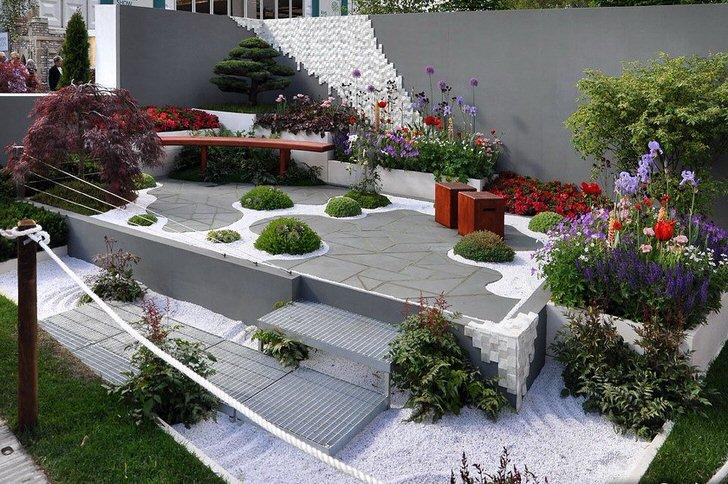 Место для отдыха в саду оформлено в стиле модерн. Участки свежей зелени на покрытии из плитки смотрятся элегантно и эксцентрично.