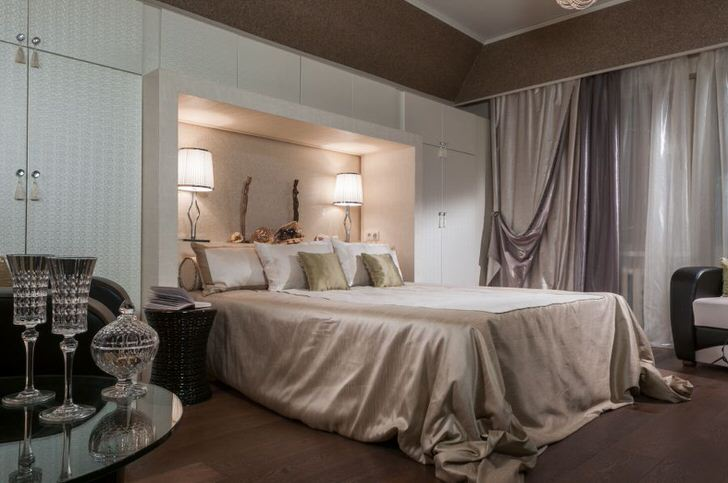 Благородный интерьер спальни в арт-деко стиле. Внимание притягивают функциональные шкафы белого цвета. Благодаря им комната становится достаточно просторной и светлой.