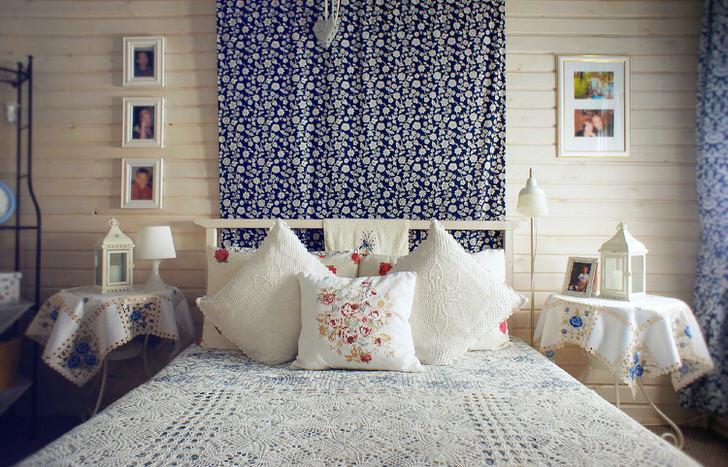 В соответствии с деревенским стилем кровать украшает множество подушек с контрастной вышивкой красного цвета. Прикроватные столики накрыты скатертью с нежными голубыми цветами.