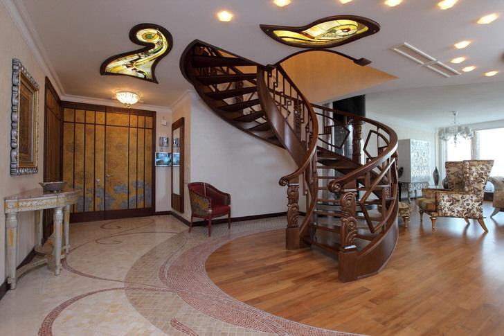 """Холл в модерн стиле с винтовой лестницей на второй этаж оборудован """"правильной"""", функциональной мебелью. Встроенные гардеробные позволяют экономить пространство и не делают его захламленным."""